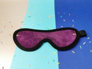 De voorkant van de blinddoek. Hij is gemaakt van paarse stof die op suede lijkt, met een zwart randje van andere stof.
