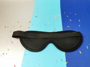 De achterkant van de blinddoek. Je ziet zwarte stof en een breed elastieken bandje.