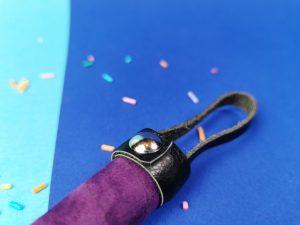 Close-up van de bovenkant van het zweepje uit de rimba soft bondage set. Je ziet dat er een leren strookje om de bovenkant van het handvat zit. Daar aan vast zit een lus, zodat je de zweep op kan hangen.