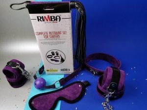 De rimba soft bondage set, de spullen liggen voor de verpakking, waar je de achterkant van ziet. Daarop staat tekst en een foto van de producten.