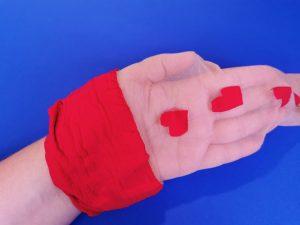 Ik heb mijn hand in de kous, zodat je kan zien dat de kous zelf doorzichtig is, maar de rode bovenband en de rode hartjes niet.