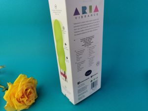 De achterkant van de verpakking van de blush aria vibrance. Je ziet op de zijkant een foto van de vibrator in het groen en op de achterkant staat veel tekst.