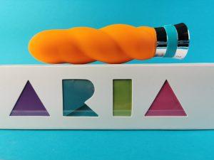 De blush aria vibrance ligt op de zijkant van de verpakking, waar je met gekleurde letters de naam aria ziet staan.