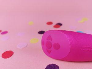 Close-up van de afstandsbediening van de we-vibe chorus. Je ziet de knopjes: een plus en een min knopje, twee knopjes die zijwaards wijzen en nog een rond knopje bovenaan.