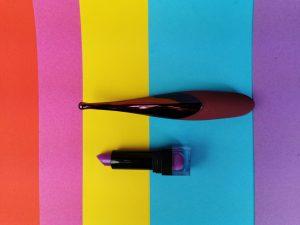 De senzi pinpoint vibrator naast een lipstick.