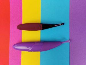 De senzi pinpoint vibrator en de zumio s liggen naast elkaar. De zumio is langer en dikker, maar qua vorm zien ze er ongeveer hetzelfde uit.