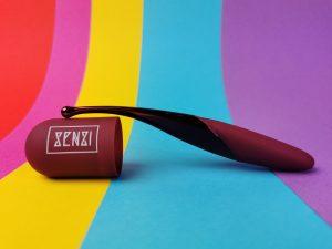 De senzi pinpoint vibrator balanceert op het dopje van het hoesje waar de merknaam senzi op staat.