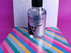 Het doorzichtige flesje sliquid spark, met zwart dopje en zilverkleurig etiket. Er voor ligt een uitgelopen druppel van het glijmiddel, wat er best dun uitziet.