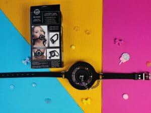 De pie hole gag met de achterkant van de verpakking, waar je een aantal foto's van de gag, ook in gebruik, ziet.
