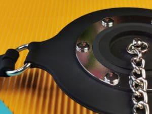 Close-up van de master series pie hole silicone feeding gag, je ziet hoe het kettinkje vast zit aan het dopje en het metalen randje om de gag de versterken.