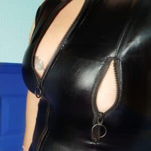Weer een close-up van tess haar decolleté in de lovehoney fierce wet look body, maar nu met het ritsje wat over de borst loopt open. En je ziet geen tepel, alleen huid.