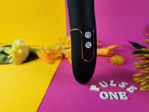 Close-up van de knopjes van de mae b pulse one. Je ziet bovenaan een wit rond knopje met het power teken. Daar onder zie je een wit rond knopje met pijltjes omhoog en naar beneden.