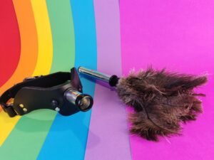 De meo humiliator mouth gag system ligt naast het feather duster attachment.